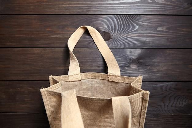 茶色の木製テーブルに再利用可能なショッピングジュートバッグ