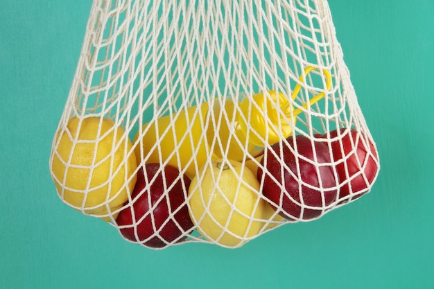 Reusable shopping mesh bag with lemons, fruits and glass bottle. zero waste, plastic free concept.