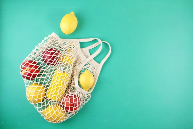 Reusable shopping mesh bag with lemons, fruits and glass bottle