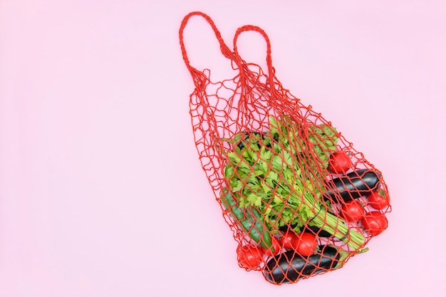 Reusable shopping mesh bag with vegetables on a pink background