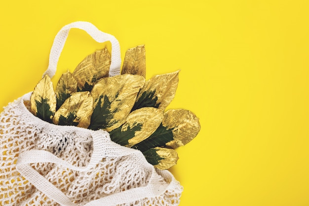 Reusable shopping net bag with green and golden leaves on yellow fall autumn background