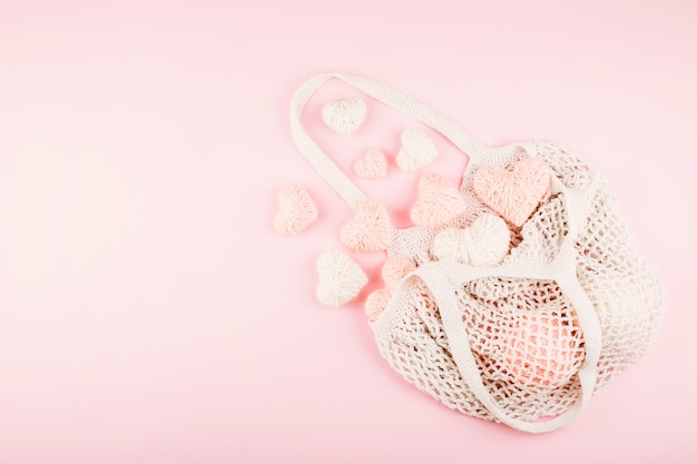 Reusable shopping net bag with white and pink knitted hearts on pastel background