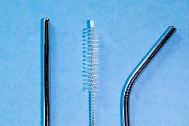 青の背景に再利用可能なステンレス鋼のストローとクリーニングブラシ、環境にやさしいライフスタイル、コピースペース、上面図、フラットレイアウト。