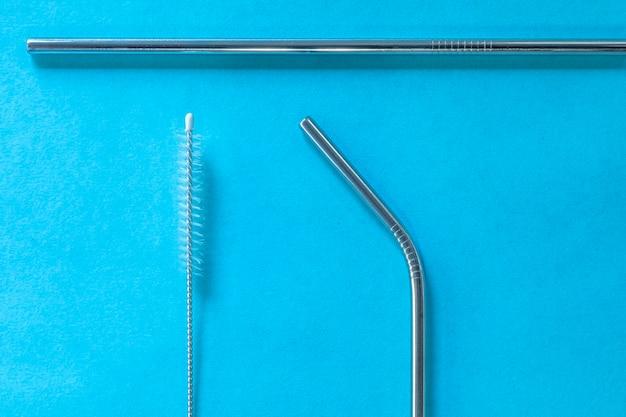 Многоразовые соломинки из нержавеющей стали и чистящая щетка на синем.