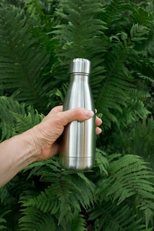 Reusable stainless thermos bottle for water in female hand to replenish the body's water reserves against the background of fern leaves.