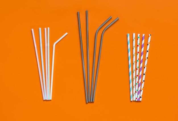 Многоразовые стальные и бумажные соломинки для питья в качестве альтернативы замене пластиковой соломинки для питья на оранжевом фоне, вид сверху