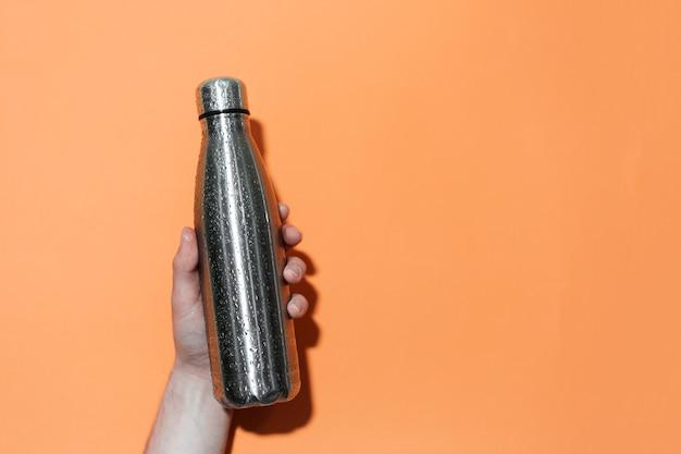 緑豊かな溶岩色の壁に男性の手で水を噴霧した再利用可能な鋼の魔法瓶。