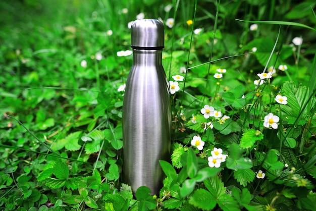緑の草の上の再利用可能な鋼の熱水ボトル