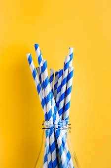 Reusable, striped straws for drinking juice or cocktail life, in a glass bottle.