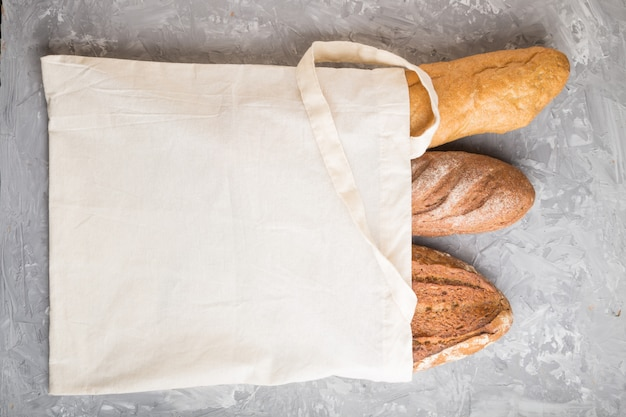 Reusable textile grocery bag with fresh baked bread on a gray concrete background. top view, copy space.