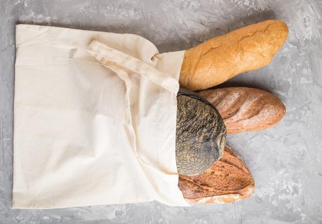 灰色のコンクリート表面に焼きたてのパンが入った再利用可能なテキスタイル食料品バッグ。上面図、フラットレイ、コピースペース