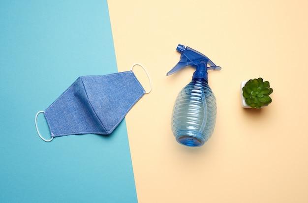 ベージュブルーの背景に消毒用の再利用可能なテキスタイルマスク、ブルーボトル