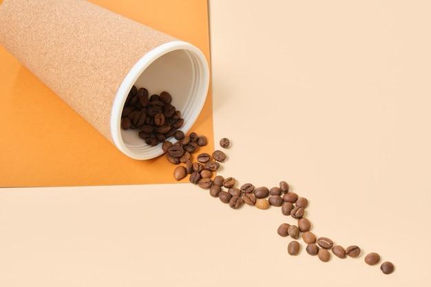 코르크와 뿌려진 커피 콩 베이지 색과 갈색 기하학적 배경 복사 공간으로 덮여 재사용 가능한 열 머그잔