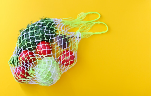Reusable white shopping mesh bag with fruits and vegetables: tomatoes, cabbage, beetroot, dill, peaches.
