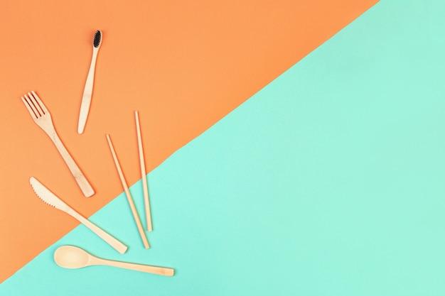 再利用可能な木製カトラリーと竹歯ブラシ。エコフレンドリーなフォーク、ナイフ、スプーン、ミントオレンジ色の背景。廃棄物ゼロのコンセプト。 copyspace。