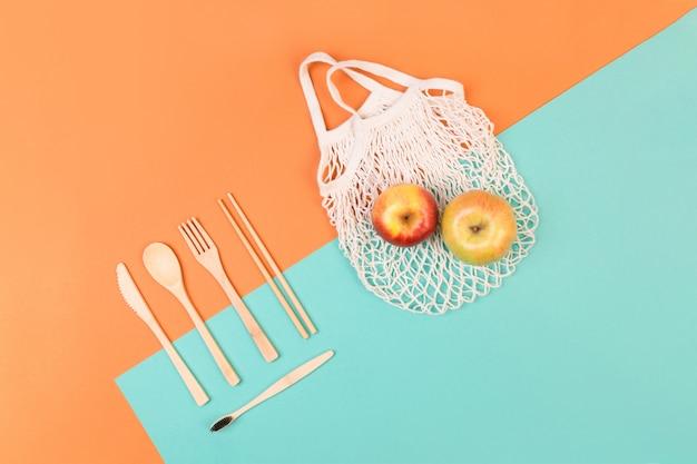 再利用可能な木製カトラリーと食料品の袋。エコフレンドリーなフォーク、ナイフ、スプーン、ミントオレンジ色の背景上のリンゴ。廃棄物ゼロのコンセプト。 copyspace。