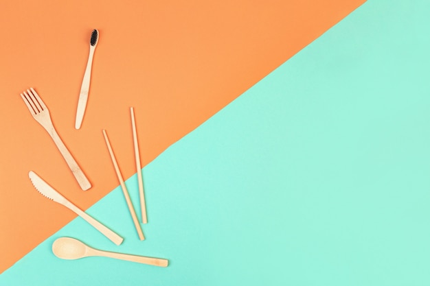 Reusable wooden cutlery and bamboo toothbrush. eco friendly fork, knife, spoon on a mint orange background. zero waste concept. copyspace.