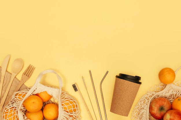 Reusable wooden cutlery, cork mug and grocery bag with fruits on yellow banner. zero waste concept.