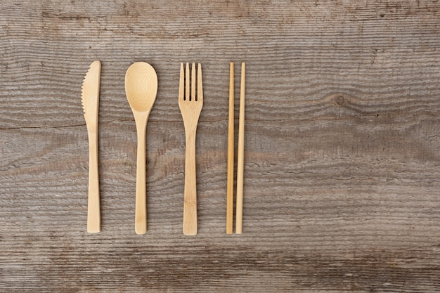 Reusable wooden cutlery. eco friendly fork, knife, spoon, sticks on an old wood