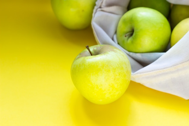 Reusable zero waste textile bag with bread and green apples