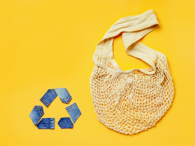 Reuse, reduce, recycle concept background. recycle symbol made from old jeans and mesh bag on yellow background.