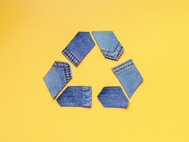 Reuse, reduce, recycle concept background. recycle symbol made from old jeans on yellow background.