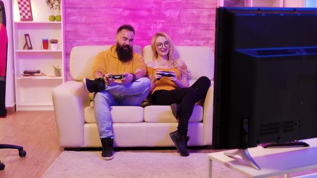 무선 컨트롤러를 사용하여 대형 스크린 tv에서 함께 비디오 게임을 하는 아름다운 젊은 부부의 영상을 공개합니다.
