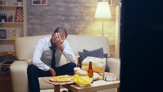 Colpo rivelatore dell'uomo d'affari in tuta che guarda una partita dopo il lavoro seduto sul divano.