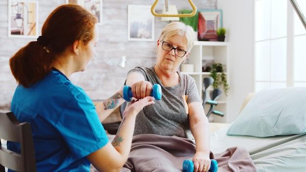 Inquadratura rivelatrice di un'infermiera che aiuta una donna anziana a recuperare i muscoli dopo un incidente. è sdraiata in un letto d'ospedale in una casa di riposo