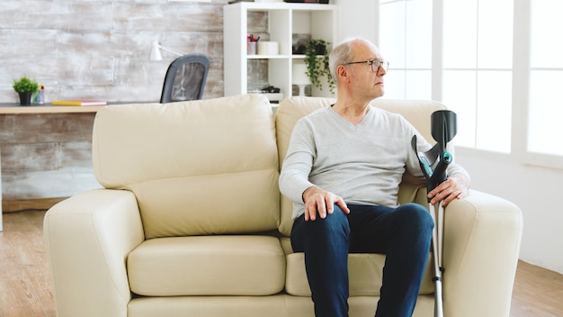 Revealing shot of male nurse checking on retired old man with alzheimer sitting on a couch in the nursing home