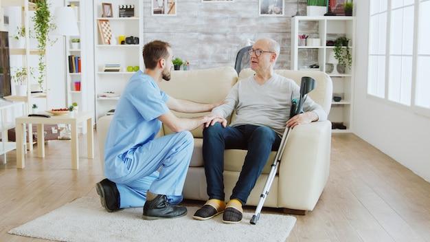 알츠하이머가 요양원의 소파에 앉아 있는 은퇴한 노인을 확인하는 남성 간호사의 사진 공개