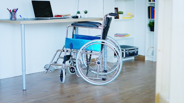 Revealing shot of wheelchair in empty room for people with disabilities.