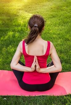 逆の祈りのヨガのポーズ。公園のマットでヨガの練習の女性
