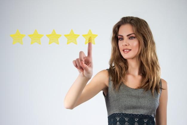 Rivedere, aumentare la classificazione o la classifica, la valutazione e la classificazione. l'uomo d'affari disegna cinque stella gialla per aumentare la rating della sua azienda