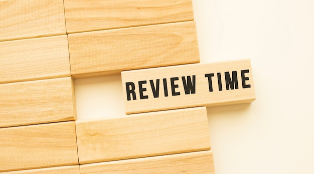 Review time text on a strip of wood lying on a white table.