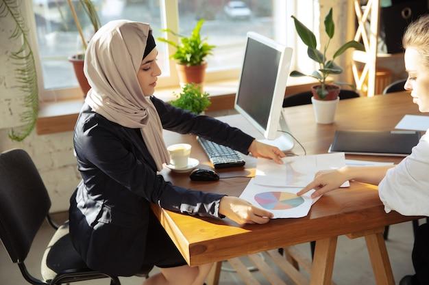 동료와 문서 검토 히잡을 쓴 아름다운 아라비아 사업가