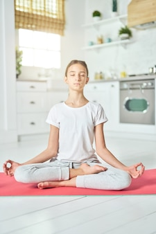 활력을 불어넣는 경험. 운동복을 입은 스포티한 히스패닉 10대 소녀는 요가를 연습하는 동안 침착해 보이고 로터스에 앉아 부엌의 매트에 포즈를 취합니다. 홈 인테리어 배경
