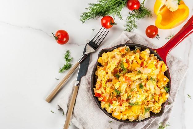 Revoltillo de huevos scrambled eggs a la dominicanaポーションフライパンの白い大理石のテーブル