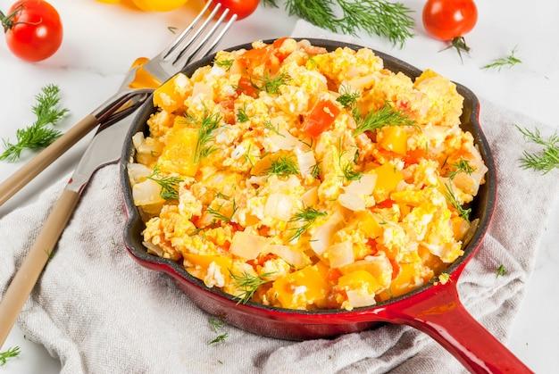 Revoltillo de huevos scrambled eggs a la dominicana in portioned skillet on white marble table