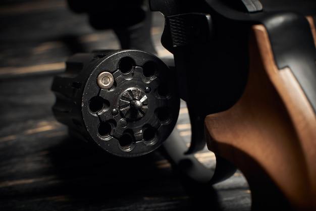 暗い木製の背景に1つのflobert弾薬4mmを備えたリボルバーシリンダー。ロシアのルーレットの概念