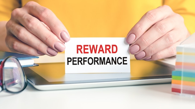 Reward performance is written on a white business card in a woman hands