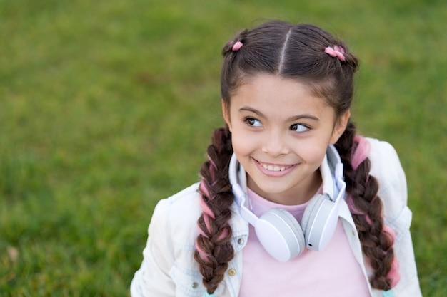 Перемотайте назад счастье. маленький меломан. маленький ребенок слушает музыку на открытом воздухе. счастливый маленький ребенок. счастливая девушка носит наушники. я всегда хожу в наушниках.
