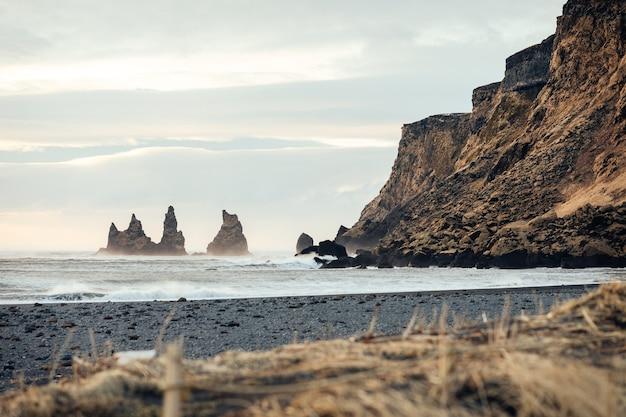 Точка зрения рейнисдрангар над пляжем с черным песком в вик, исландия