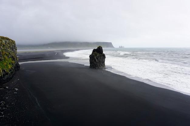 Вулканический пляж рейнисфьяра с черным песком в дождливый день. вик, исландия.