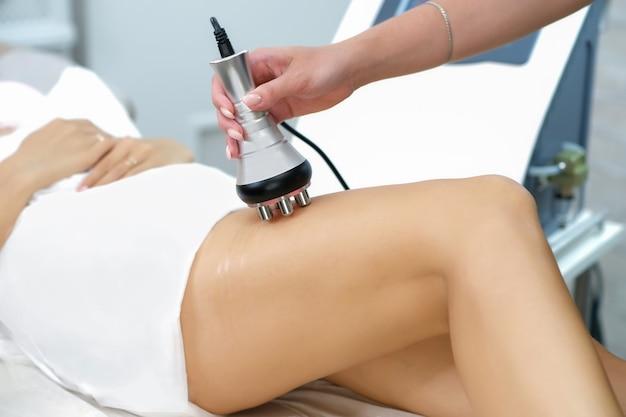 若い女性の足のrfリフティングハードウェアマッサージ。セルライト溶液と減量