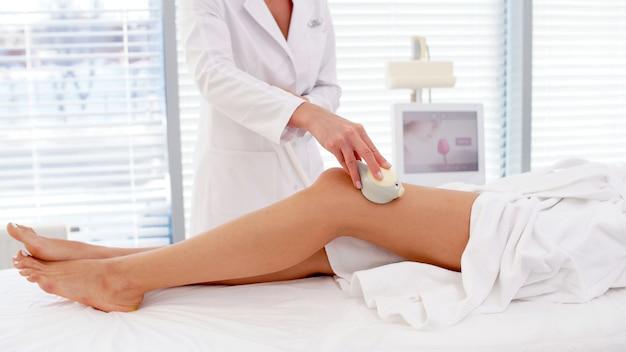 Процедура rf-лифтинга на женских ногах в салоне красоты крупным планом
