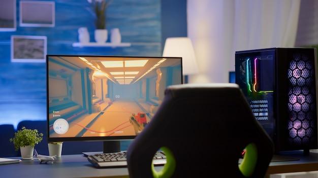 화면에 1인칭 슈팅 게임이 있는 rgb 강력한 개인용 컴퓨터 게이머 장비. 모니터는 홈 게임룸의 테이블 위에 있습니다. 현대적인 디자인의 아늑한 객실은 따뜻한 네온 불빛으로 밝혀졌습니다.