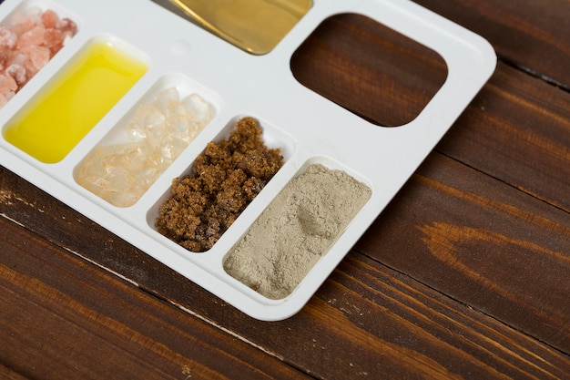 Rhassoul clay; coffee grounds; rock salt and oil on white tray against wooden table