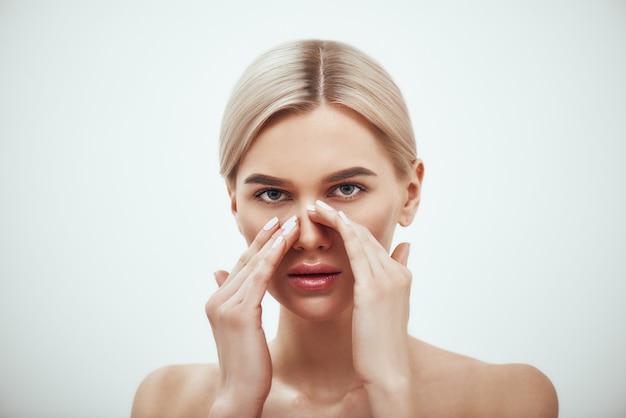 彼女の鼻に触れてカメラを見ている魅力的な金髪の女性の鼻形成術の鼻の手術の肖像画