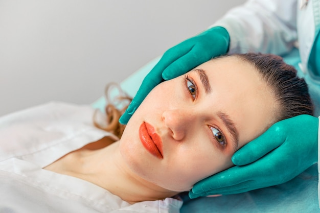 Rhinoplasty, the surgeon hands touches the patient s nose. people, cosmetology, plastic surgery and beauty concept - surgeon or cosmetologist hands touching female face. copy space.